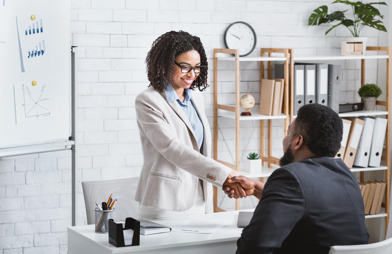 Comment utiliser LinkedIn pour trouver un job en 2021 ? Un responsable du recrutement serre la main d'un candidat à un poste vacant après un entretien de travail dans un bureau moderne, salle de photocopie